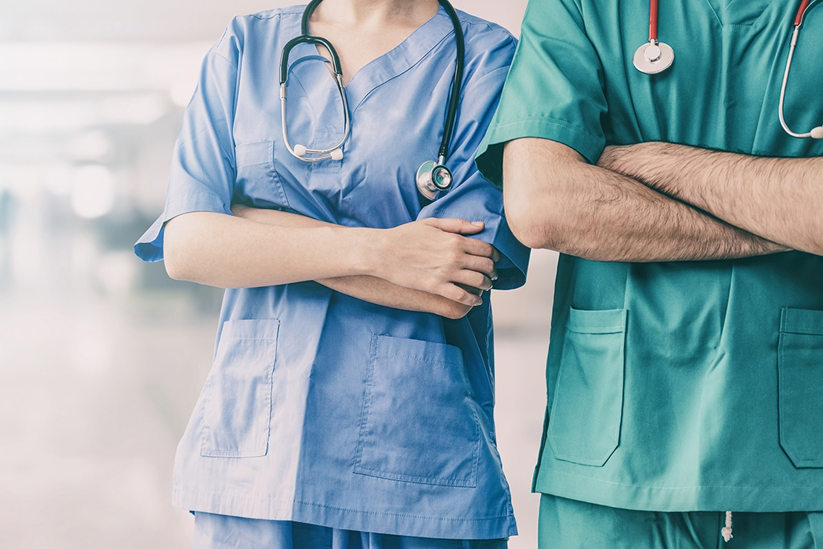 Two hospital staffs - surgeon, doctor or nurse standing with arms crossed in the hospital. Medical healthcare and doctor service.
