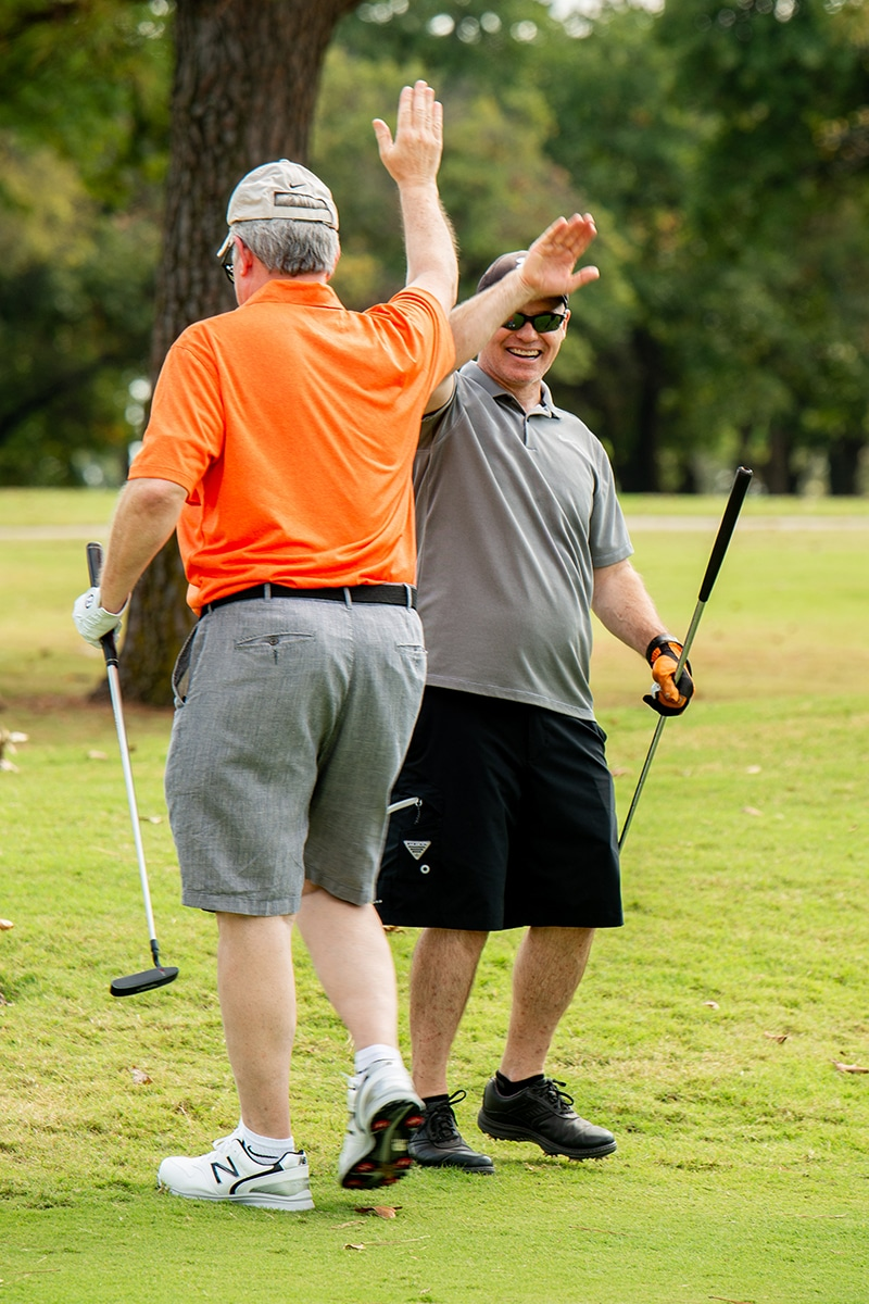 golfers high five on course