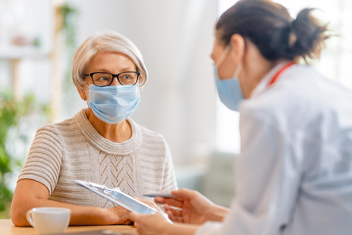 Senior woman listening to doctor both wearing facemasks